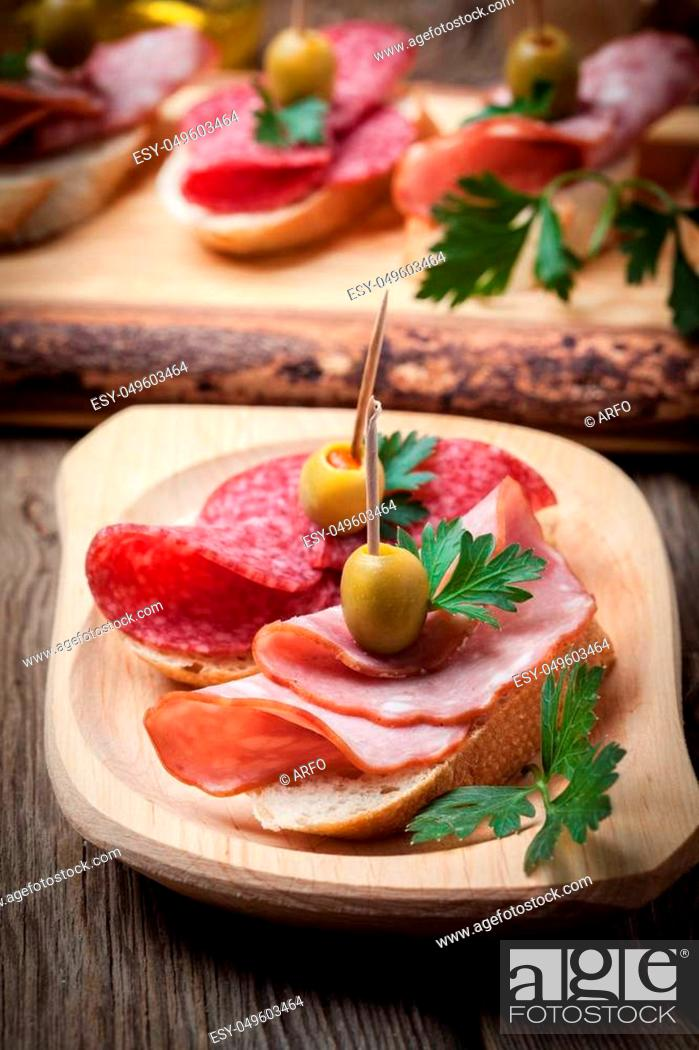 Stock Photo: Spanish cuisine. Tapas with sliced sausage, salami, olives and parsley on a wooden table.