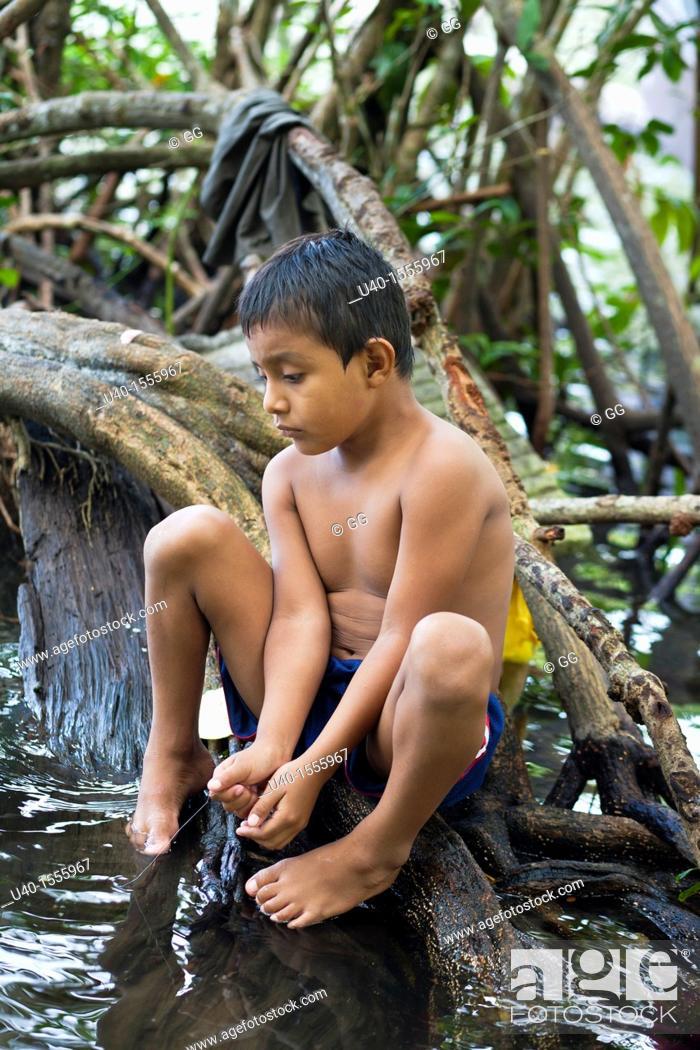 Stock Photo: Guatemala, Rio Dulce, boy fishing in river.