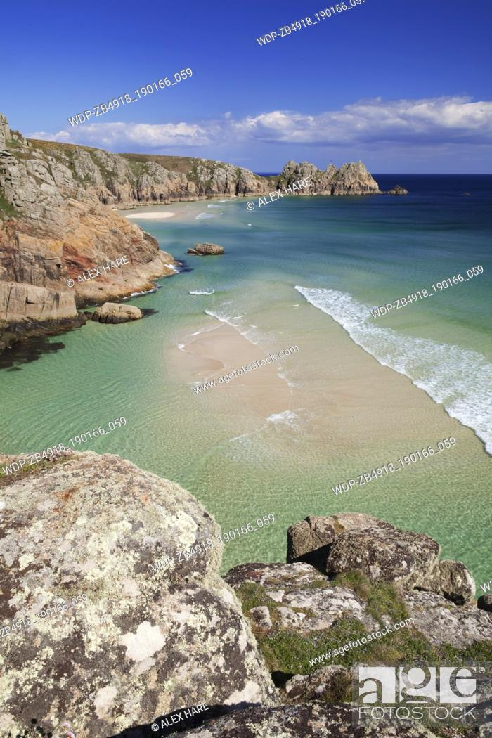 Photo de stock: A view of the sandy beach at Porthcurno with Logan rock in the distance.