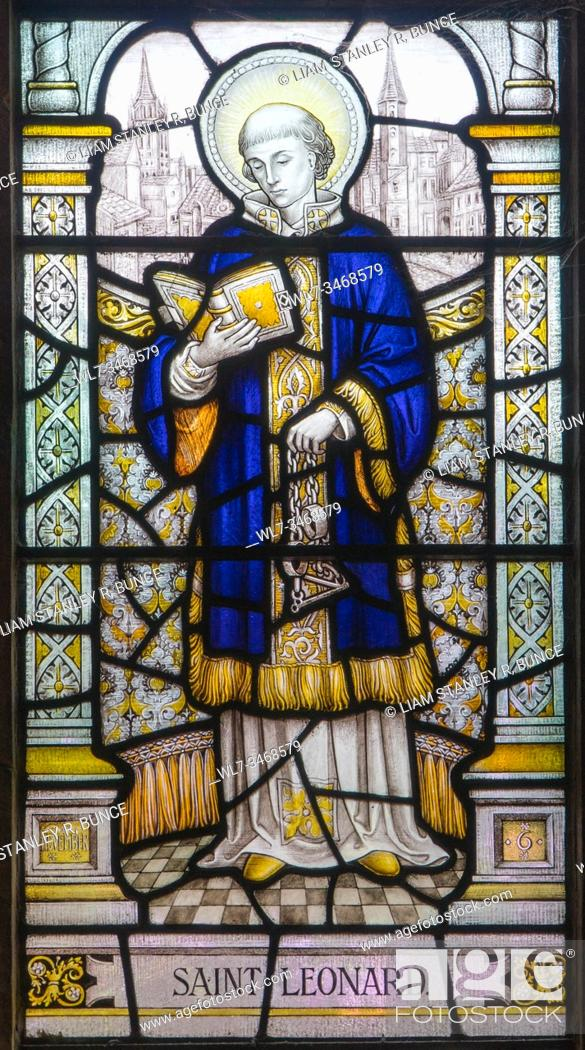 Stock Photo: Stained glass depicting St Leonard of Noblac holding manacles Chester Cathedral Cheshire UK. May 2019.