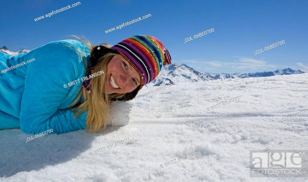 Stock Photo: Girl laying on snow, smiling.