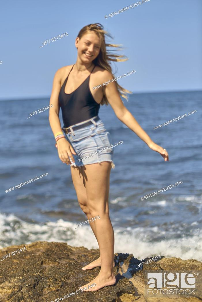 Photo de stock: young woman at seaside enjoying holiday, sunny weather and freedom, in Crete, Greece.