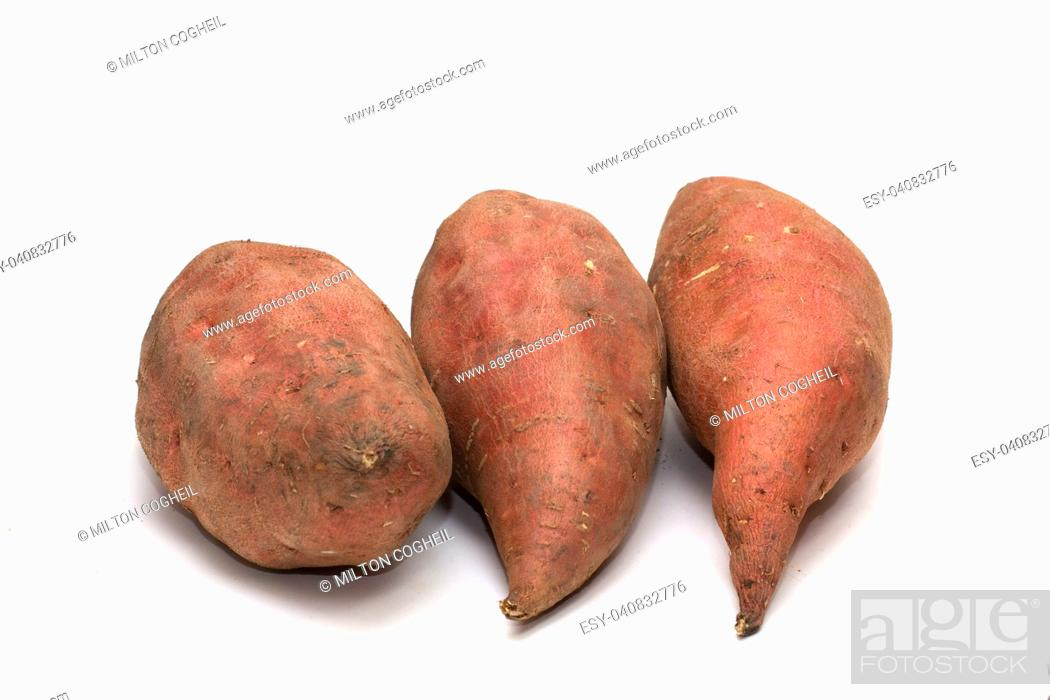 Stock Photo: An arrangement of raw sweet potato tubers on a white background.
