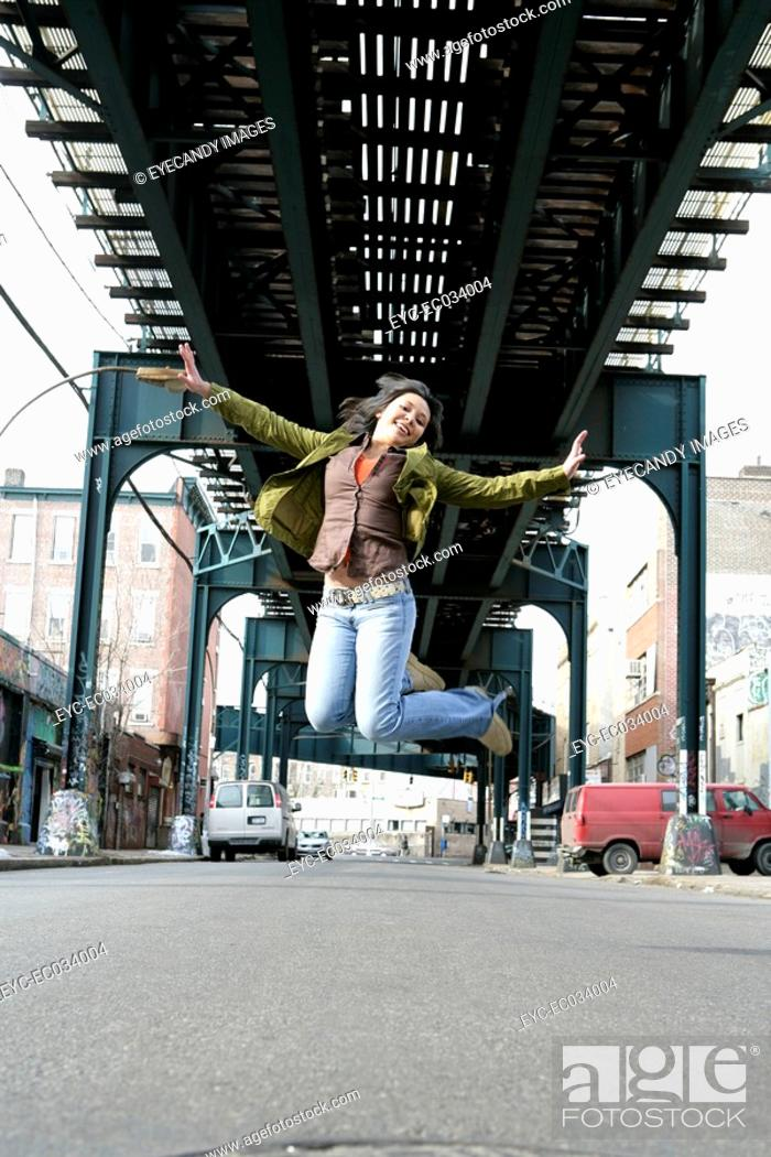 Stock Photo: View of a young woman jumping.