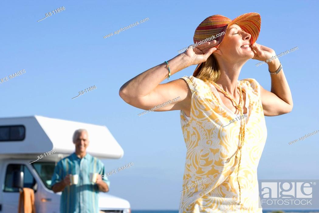 Stock Photo: Mature woman with hands on hat by motor home on beach, husband in background, low angle view.