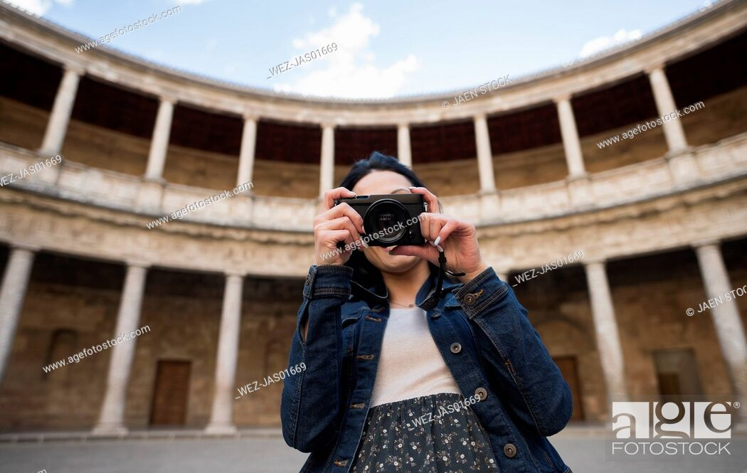 Imagen: Spain, Granada, young woman taking pictures at the Alhambra.