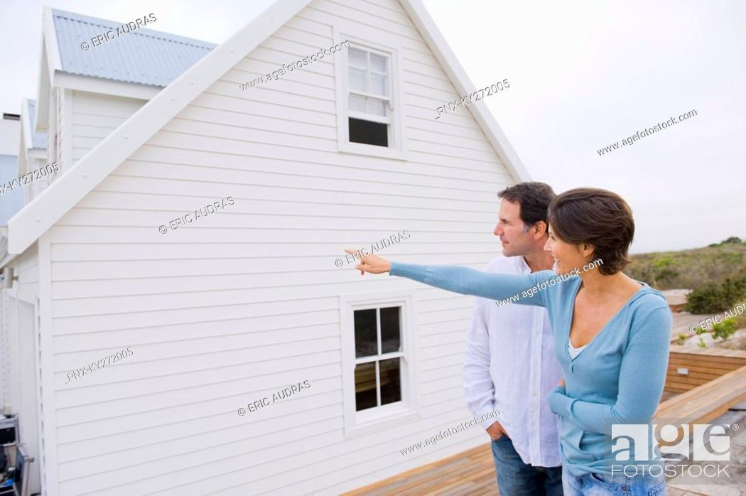 Stock Photo: Woman pointing towards a house with a man standing beside her.