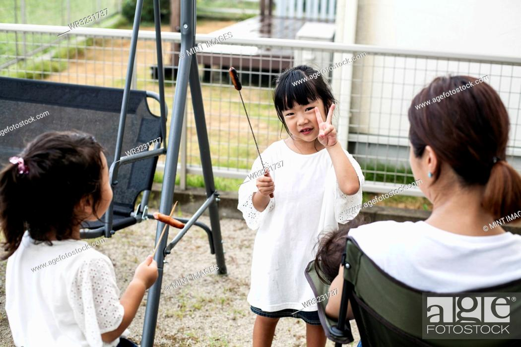 Stock Photo: Two Japanese girls holding sausages on skewers and woman in a backyard.