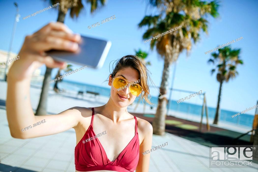 Stock Photo: Young woman wearing yellow sunglasses taking a selfie on boardwalk.
