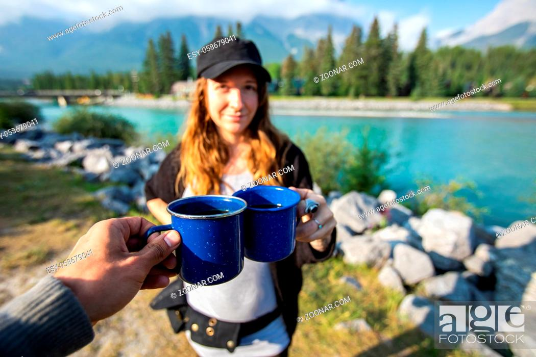 Stock Photo: Selective focus photo of a person clinching a cup of coffee or tea with a young female standing in front of a river with mountains.