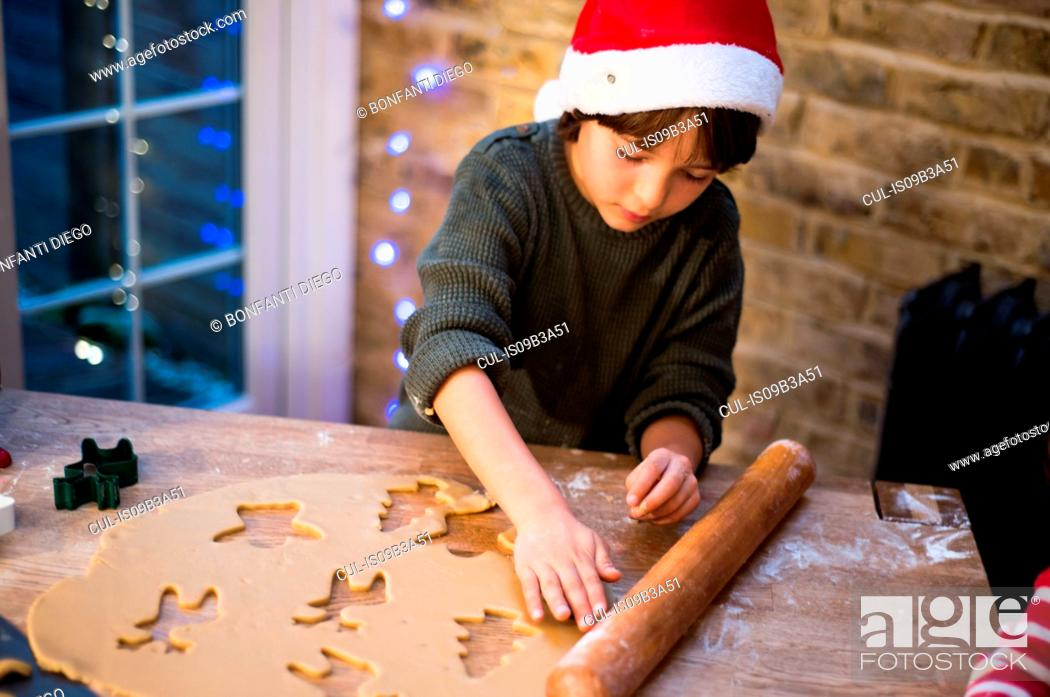 Stock Photo: Boy in Santa hat preparing Christmas cookies at kitchen counter.