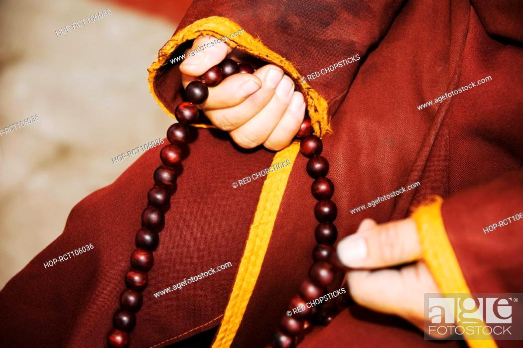 Stock Photo: Mid section view of a person's hand holding a prayer beads, Da Zhao Temple, Hohhot, Inner Mongolia, China.