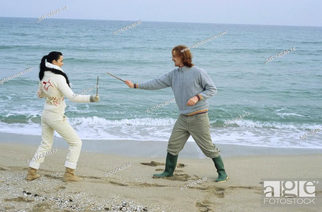 Stock Photo: Young Couple fighting with little Sticks - Imitation of a Swordplay - Fun - Leisure Time - Beach.