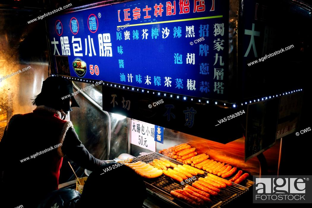 "Imagen: Shilin Night Market, Taipei, Taiwan - Close up of many sausages on the grille, it's a yammy Taiwanese snack named """"Small sausage in big sausage""""."