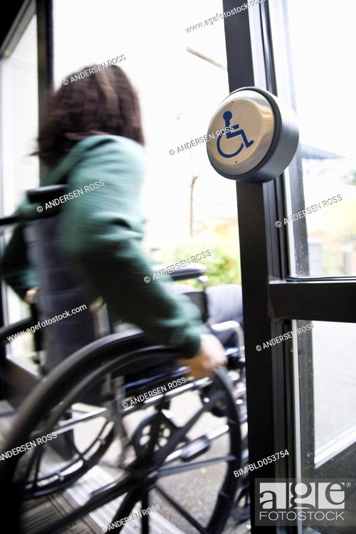 Stock Photo: African man in wheelchair using automatic door.