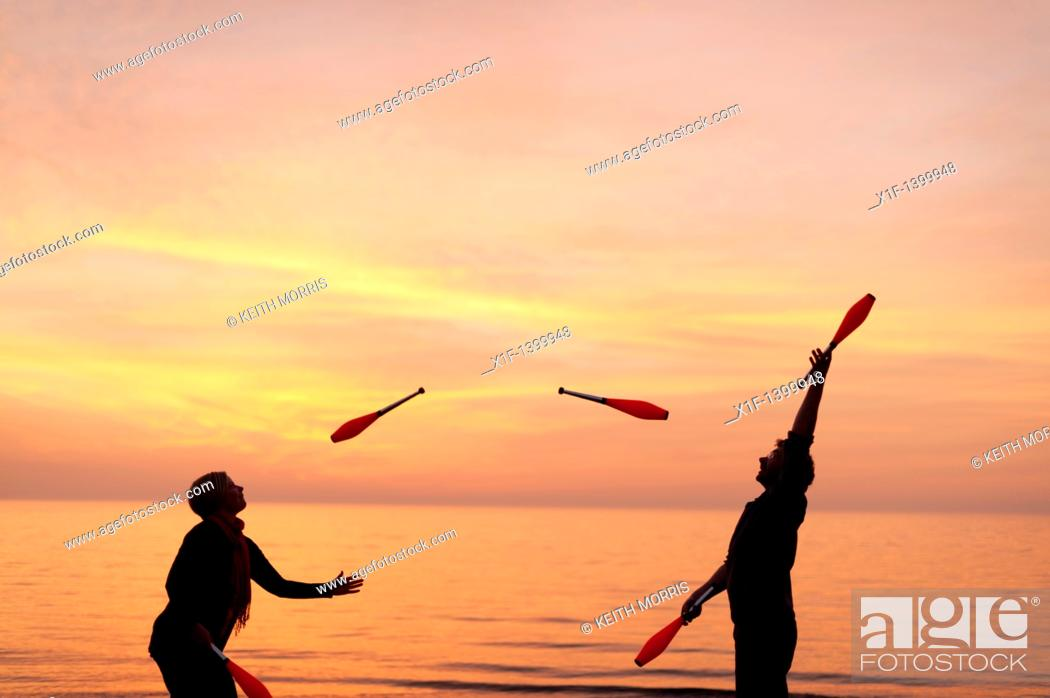 Stock Photo: A young couple Juggling with clubs on the beach, spring evening sunset, Aberystwyth Wales UK.