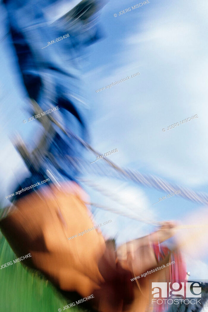 Photo de stock: A boy, 5-10 years old, swinging outside in the garden in summer, blurred.