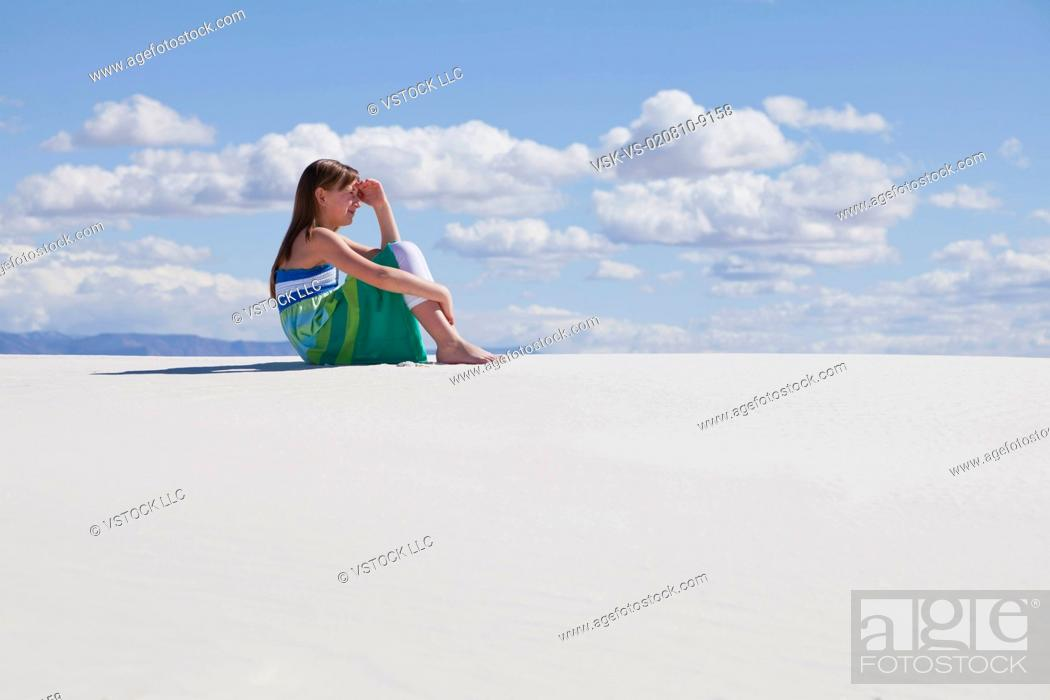Stock Photo: USA, New Mexico, Whitesands, Girl 10-11 sitting on desert and looking away.