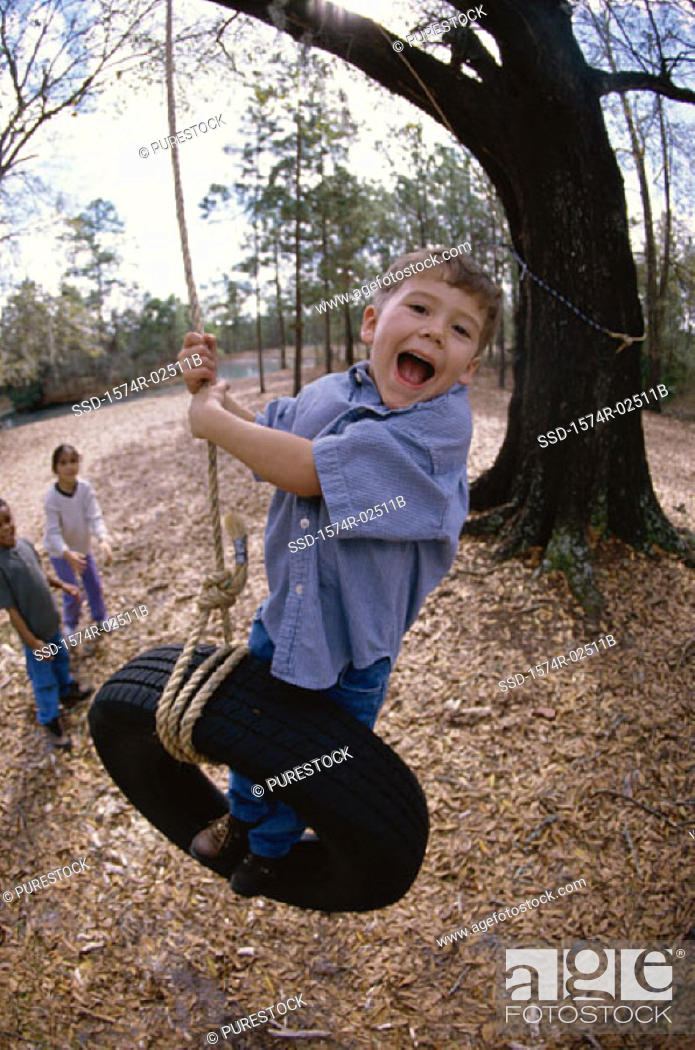 Stock Photo: Boy swinging on a tire swing.