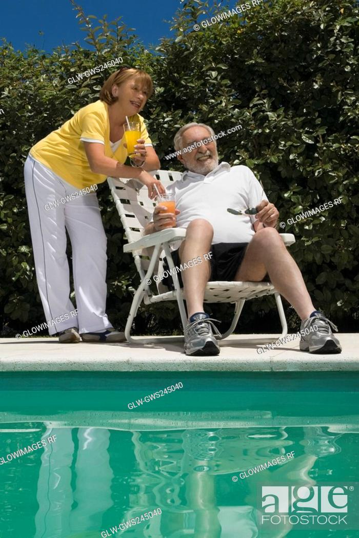 Stock Photo: Senior couple holding glasses of juice at the poolside.