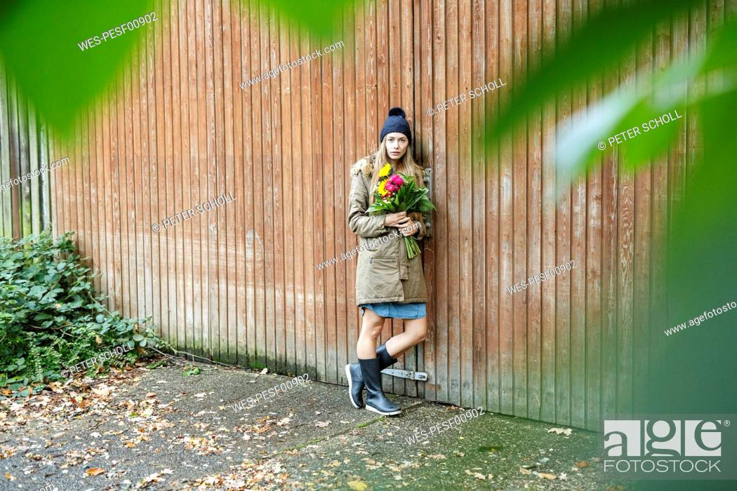 Photo de stock: Portrait of young woman standing at wooden wall holding bunch of flowers.