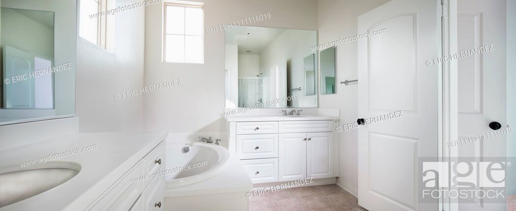 Imagen: View of a contemporary white bathroom with bath; sink and mirror at home; Ontario; California; USA.