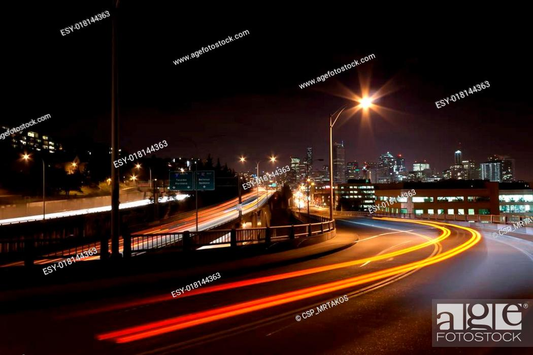 Stock Photo: Seattle night scene with light trails from passing cars on I5 and overpass.