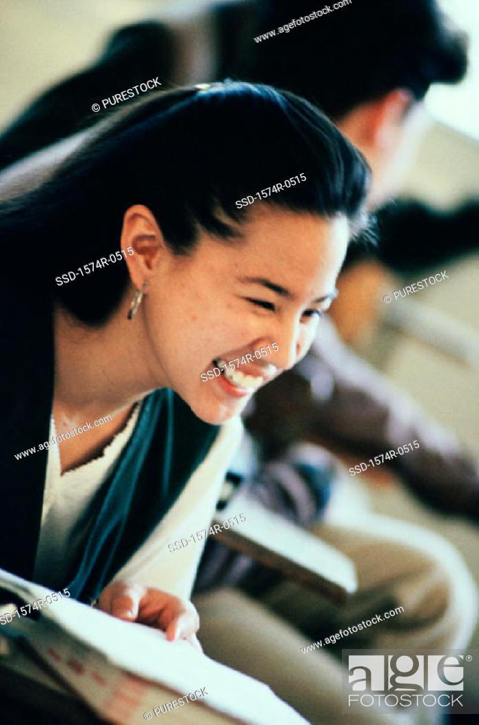 Stock Photo: Teenage girl smiling in class.