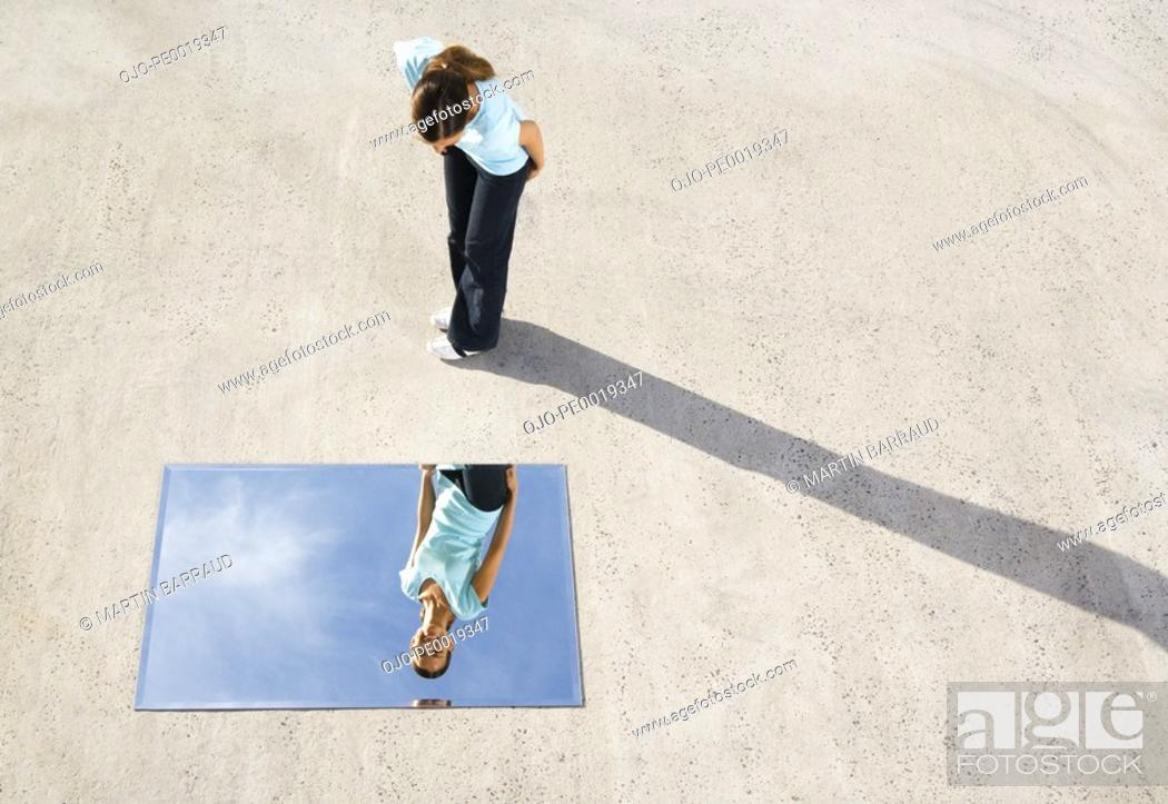Stock Photo: Woman standing above mirror and reflection outdoors.