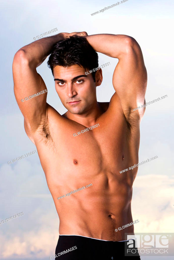 Stock Photo: Portrait of a young man standing with his hands behind his head.