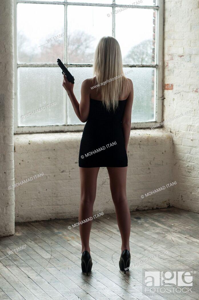 Stock Photo: Woman holding a gun.