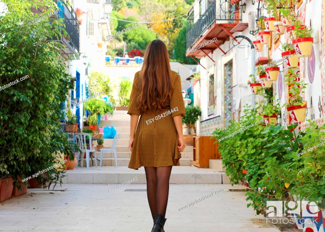 Stock Photo: Curious young woman walking in old street of Alicante, Spain. Rear view of happy cheerful girl visiting southern Europe.