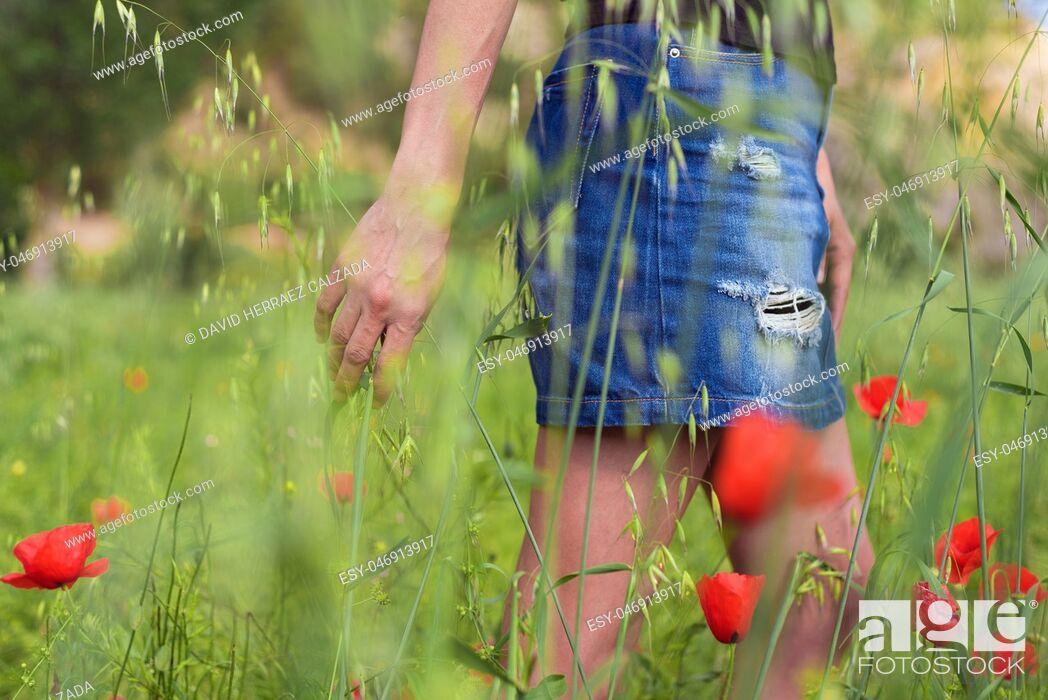 Photo de stock: Woman enjoying a walk in a poppy field under the summer sun.