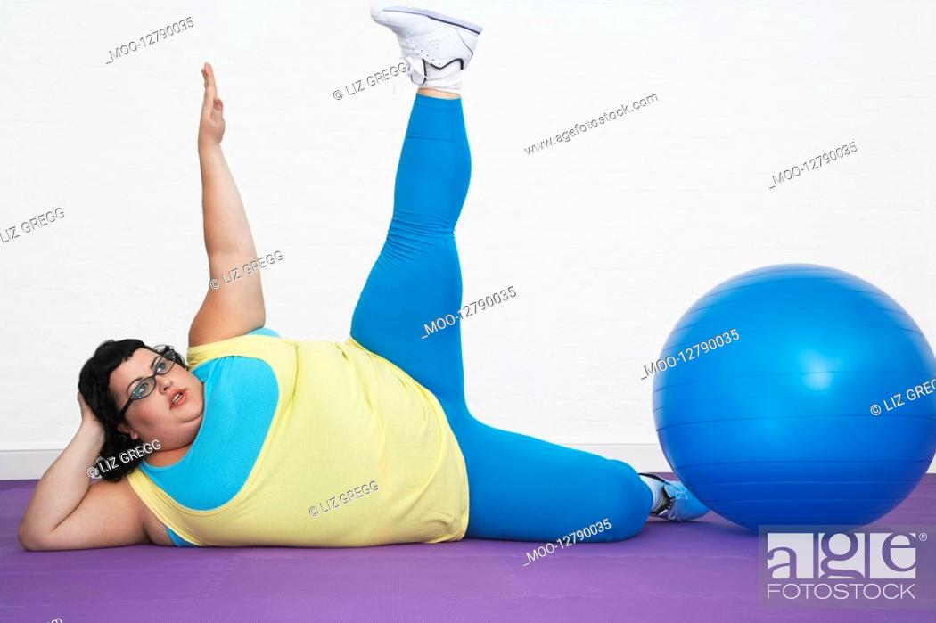 Stock Photo: Overweight Woman lying by exercise ball stretching arm and leg upwards.