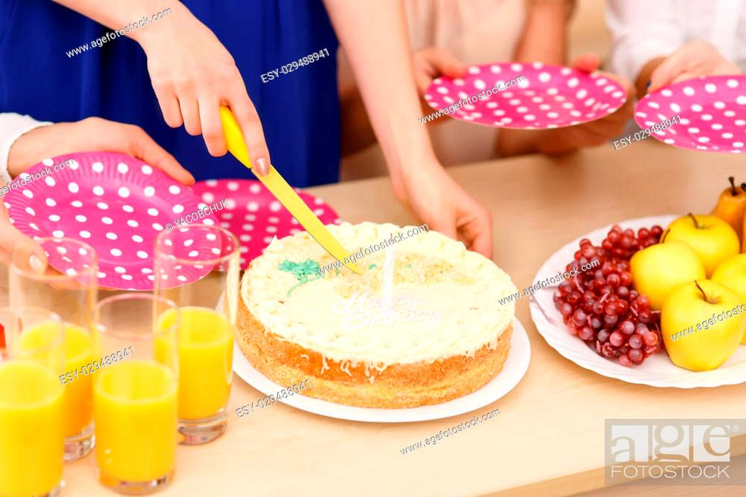 Stock Photo: Cutting the cake. Close up of girls cutting and sharing birthday cake.