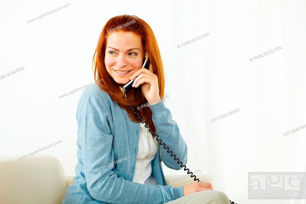 Stock Photo: Portrait of a young pretty lady using a phone and smiling.