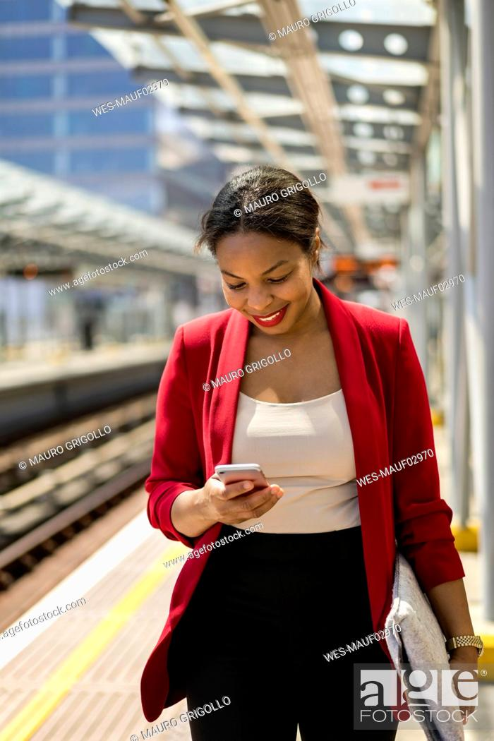 Stock Photo: Smiling businesswoman on platform looking at mobile phone, London, UK.
