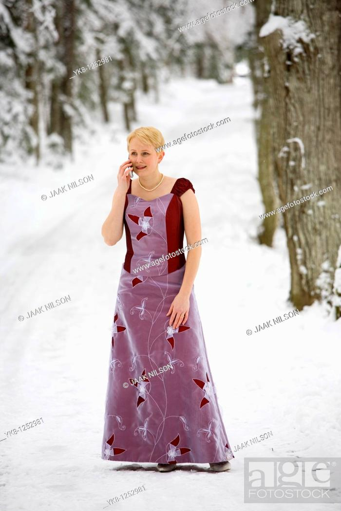 Stock Photo: Young Woman in Wedding Dress Talking on Cell Phone.