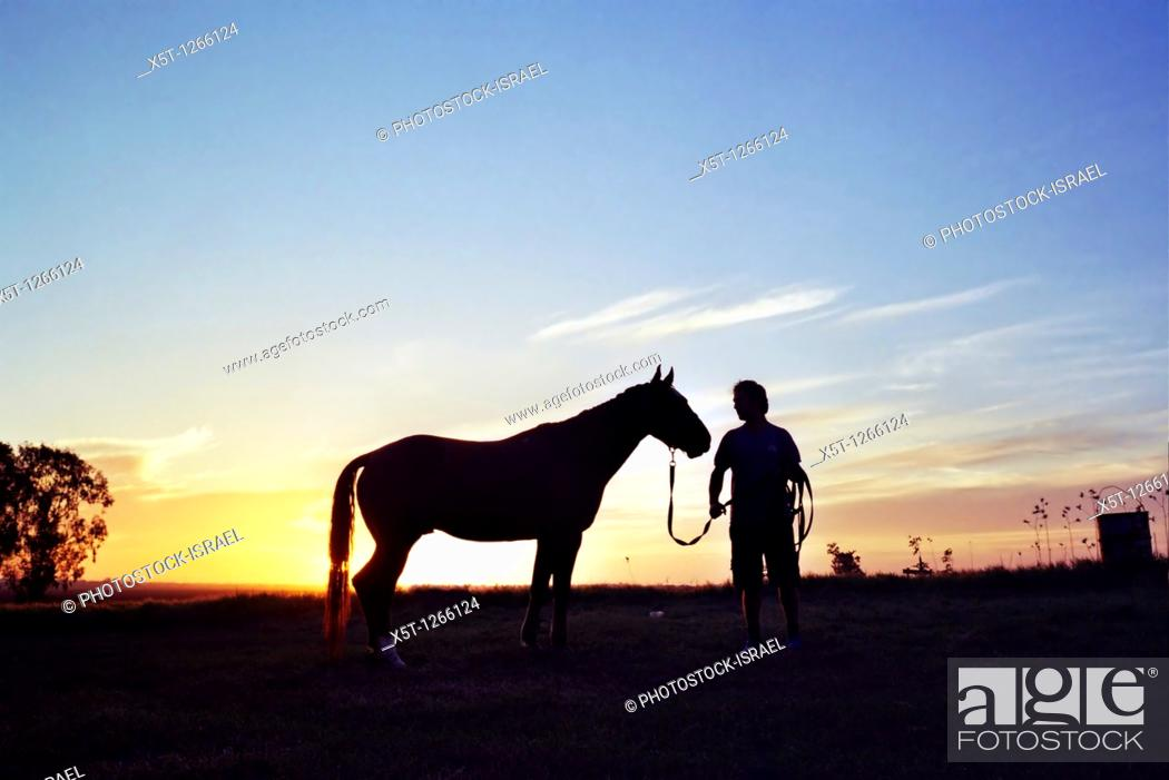 Stock Photo: Silhouette of a man and his horse at sunset.