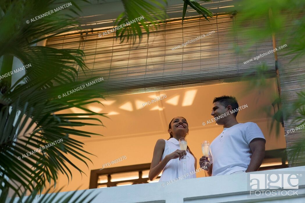 Stock Photo: Singapore, Two young people standing on balcony, holding champagne.