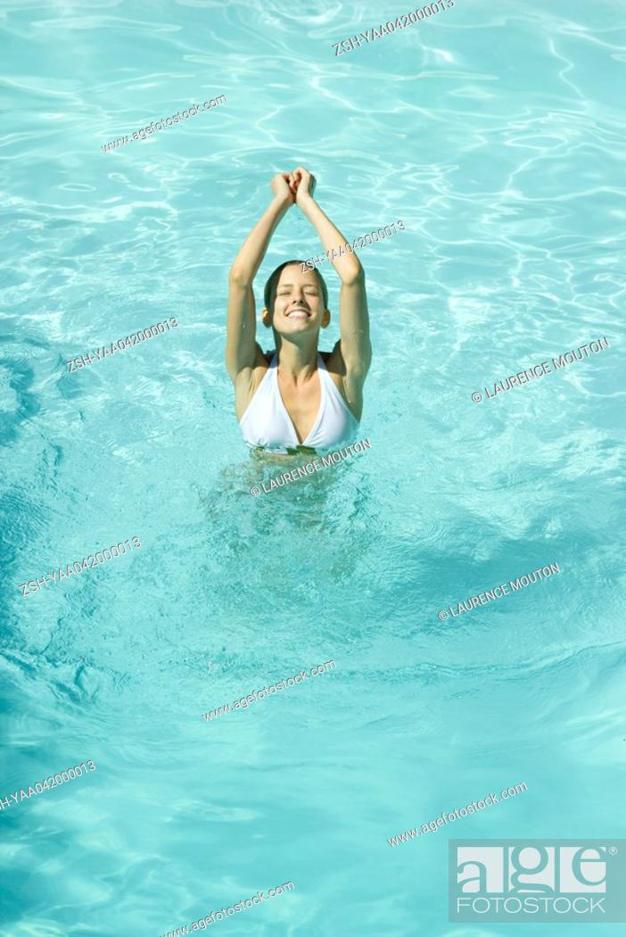 Stock Photo: Young woman standing with arms up and eyes closed in pool.