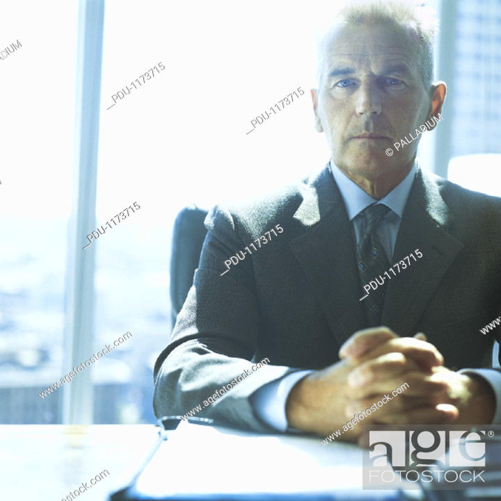 Stock Photo: Portrait of a Serious Ceo Sitting at His Desk With His Hands Together.