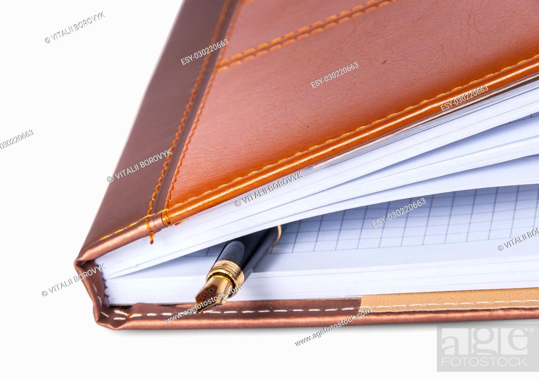 Stock Photo: Closeup fountain pen located inside the notebook isolated on white background.