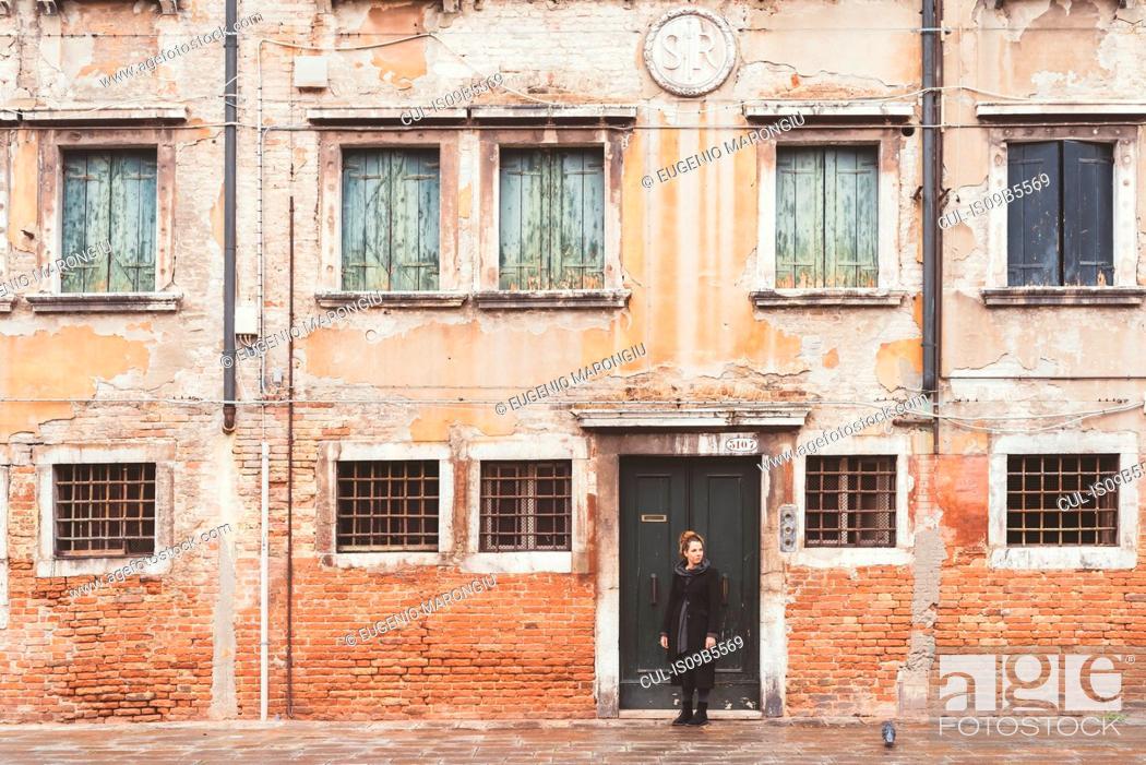 Imagen: Young woman looking over her shoulder from old doorway, Venice, Italy.
