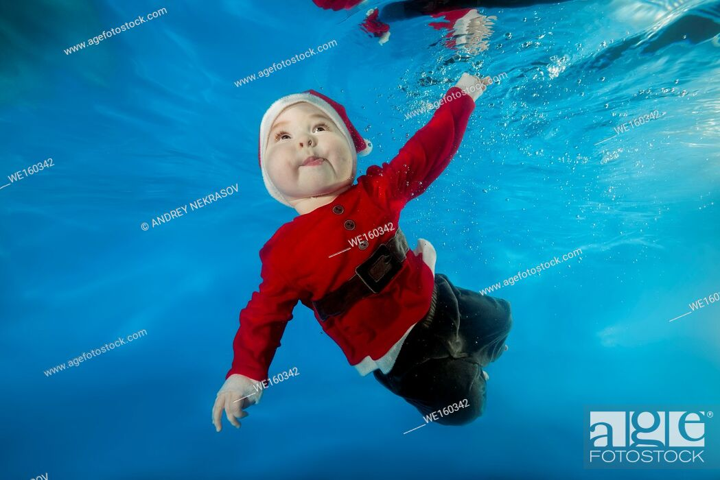 Stock Photo: A little boy in Santa's cost swims underwater in the pool.
