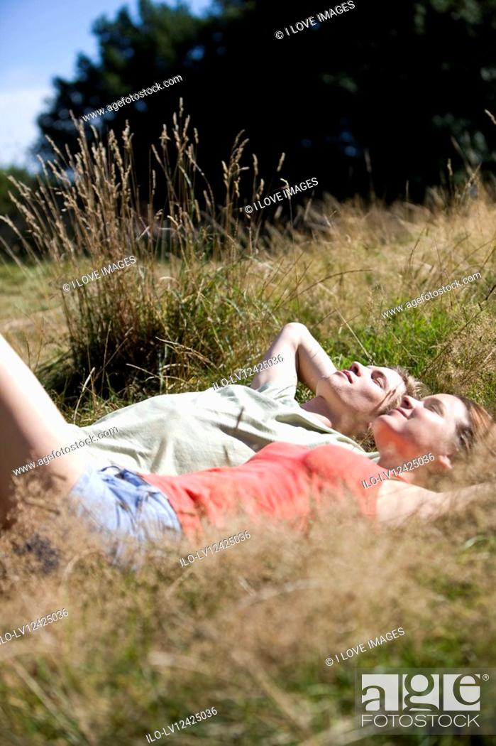 Stock Photo: A young couple lying on the grass, relaxing.