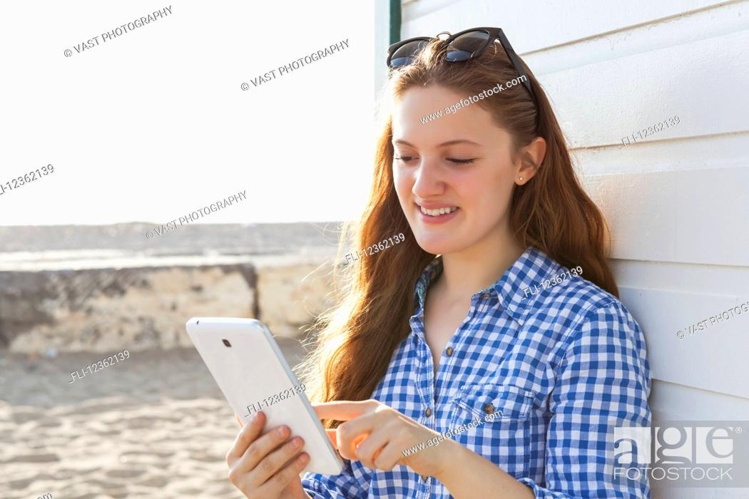 Stock Photo: Girl using tablet at Woodbine beach in summer; Toronto, Ontario, Canada.