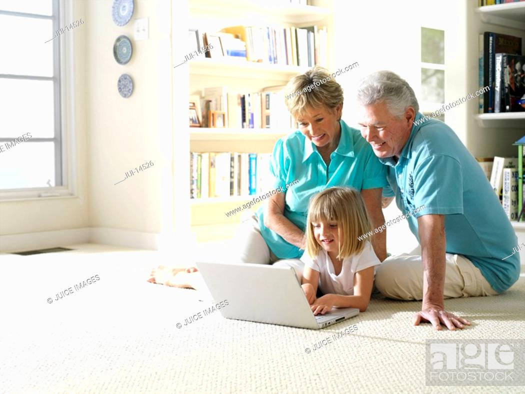 Stock Photo: Grandparents with granddaughter 6-8 using laptop computer on floor, smiling.