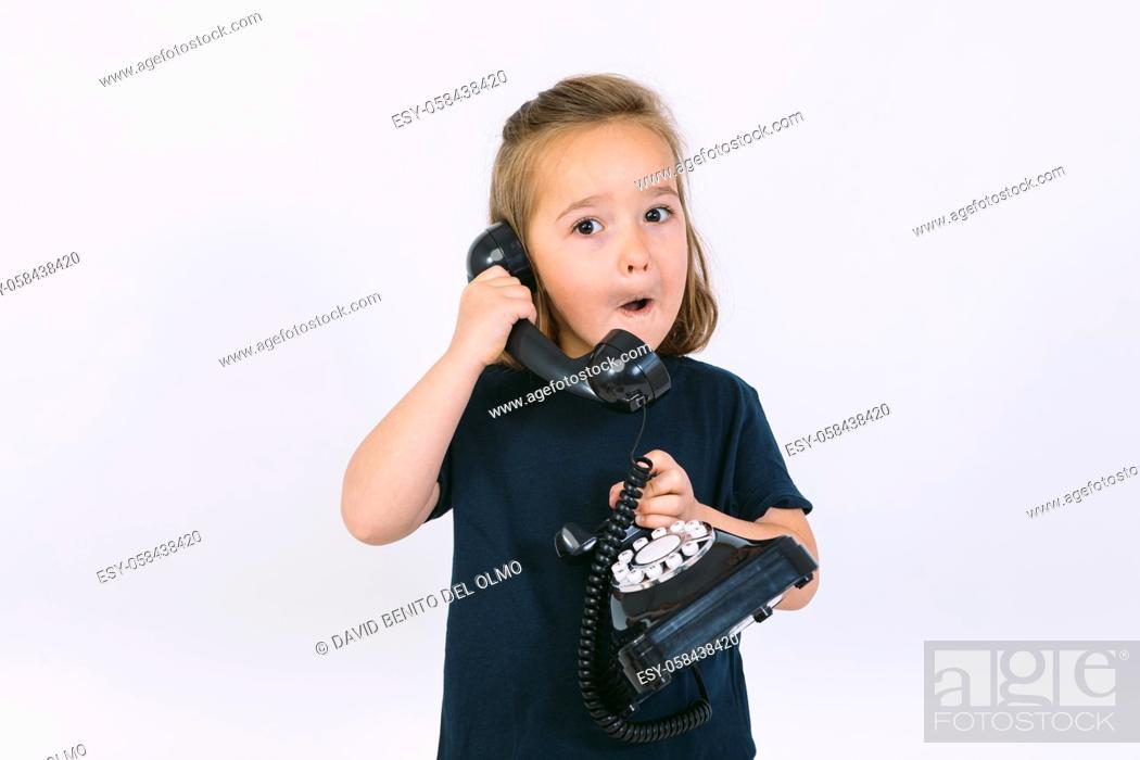 Stock Photo: Little blonde girl talking on her retro phone.