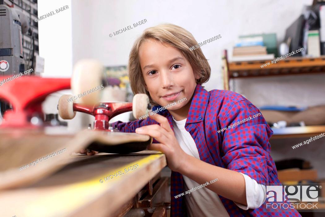 Stock Photo: Germany, Leipzig, Boy repairing skateboard, portrait.